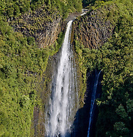 An aerial view of a gushing waterfall feeding the lush forests of Kauai.
