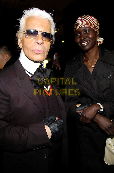 KARL LAGERFIELD & ALEK WEK.Fourth Day of the Milan Fashion Week (Milano Moda Donna) Tod's Party Woman's Collection autumn/winter 2006/07, Milan, Italy..February 21st, 2006.Ref: Garofalo/Omega/Capital Pictures.Ref: G/OME.4th half length black coat white purse bag headscarf sunglasses shades.www.capitalpictures.com.sales@capitalpictures.com.© Capital Pictures.