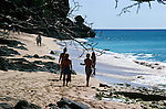 Walking along beach, one man is holding speargun, Barbados, Caribbean