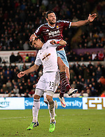 Pictured: Andy Carroll of West Ham jumps over Federico Fernandez of Swansea Saturday 10 January 2015<br />