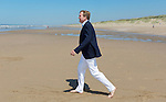 King Willem-Alexander of the Netherlands walks on the beach during a photo session on the beach near Wassenaar, the Netherlands, July 10, 2015. © Michael Kooren