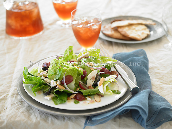 Salad with romaine lettuce, grapes, red onions, almonds, and cheese, with iced drinks and flatbread in background.