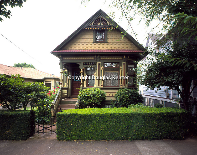 "Portland, Oregon. c.1890.  This miniature Queen Anne jewel sparkles with a wealth of gingerbread ornament and stained glass, and is painted in a proper, late nineteenth century ""autumn"" palate of greens, crème, burgundy and gold, accented with a barn-red shake roof.  But this house was not always such an eye-catcher.  When the owners first purchased it nearly 20 years ago, it had seen more than its share of updating.  Red, composition siding with yellow trim covered the exterior, a Colonial Revival front door had replaced the original, and any traces of original gingerbread trim had long ago been thrown on the scrap heap.  Bought for only $30,000, the owners planned to simply renovate the home and then resell it.  But once they became involved in the restoration process, they found they were ""hooked"" and rather than selling their Victorian cottage, they meticulously restored it and have now even begun their own restoration business."