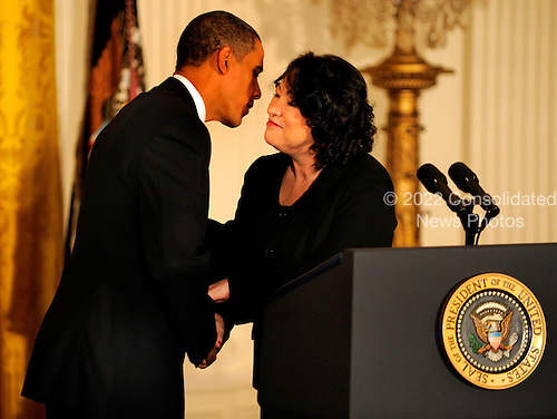 Washington, DC - August 12, 2009 -- United States President Barack Obama (L) leans in to kiss Supreme Court Justice Sonia Sotomayor after she made remarks during a reception to honor her recent swearing in, in the East Room of the White House in Washington, DC, USA August 12, 2009.     .Credit: Mike Theiler - CNP