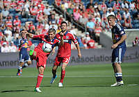 Chicago midfielder Logan Pause (12) clears the ball as New York midfielder Jan Gunnar Solli (8) looks on.  The Chicago Fire defeated the New York Red Bulls 3-1 at Toyota Park in Bridgeview, IL on June 17, 2012.