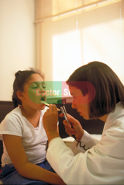 doctor examining throat of young female patient with lighted instrument