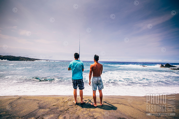 Two friends fish while camping at a remote beach in Ocean View, Hawai'i Island.