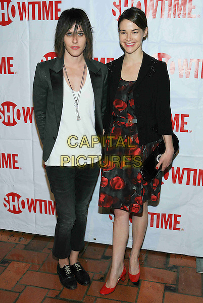 KATHERINE MOENNIG & LEISHA HAILEY  .Showtime Exclusive Star-Studded TCA Party held at the Roosevelt Hotel, Hollywood, California, USA..January 14th, 2009.full length black jacket jeans denim white top red pattern dress floral print shoes clutch bag .CAP/ADM/TC.©T. Conrad/AdMedia/Capital Pictures.