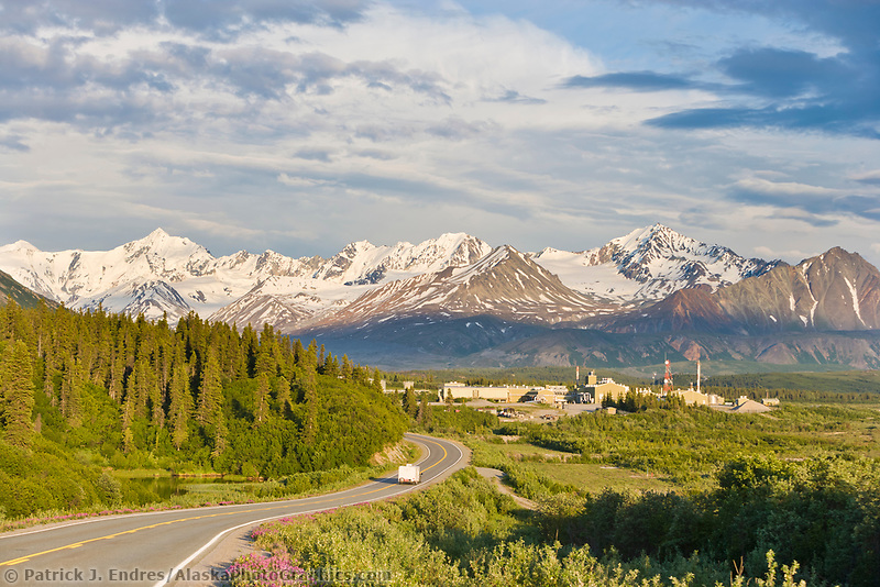 Vehicles travel along the Richardson Highway, Trans Alaska oil pipeline pump station in the distance.