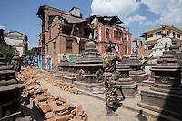 A Nepali army soldier taking photos of the destroyed Shoyembho temple, just outside Kathmandu, Nepal