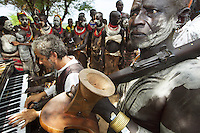 "Ethiopia. Southern Nations, Nationalities, and Peoples' Region. Omo Valley. Korcho Village. Kara tribe. Agro-pastoralist group. The Kara men are best known for the elaborate body painting they indulge in before important ceremonies. They paint their faces and bodies in white chalk and pierce their ears in five places. Scarification plays an important role in Kara body decoration. Every man carries a wooden headrest which doubles as a stool. Marc Vella is a french musician and a nomadic pianist. Over the last 25 years he has travelled with his Grand Piano in around forty countries to celebrate humanity. Thanks to the variacordes which he has devised, his piano music is unique. Creator of ""La Caravane amoureuse"" (The Caravan of Love) he takes people with him to say ""I love you"" to others and ""lovingly conquered"" their hearts and souls. Marc Vella and a Karo woman play an improvised duet-playing - one piano and four hands. The Omo Valley, situated in Africa's Great Rift Valley, is home to an estimated 200,000 indigenous peoples who have lived there for millennia. Amongst them are 1,000 to 2,000 Karo who dwell on the eastern banks of the Omo river. Southern Nations, Nationalities, and Peoples' Region (often abbreviated as SNNPR) is one of the nine ethnic divisions of Ethiopia. 8.11.15 © 2015 Didier Ruef"