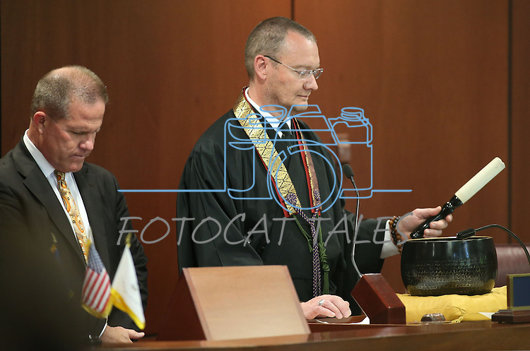 Nevada Lt. Gov. Mark Hutchison, left, listens as Rev. Matthew Fisher gives the benediction on the Senate floor at the Legislative Building in Carson City, Nev., on Tuesday, April 28, 2015. <br /> Photo by Cathleen Allison