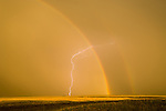 Rainbow with secondary bow and a lighting strike as the thunderstorm clears over Colorado's Great Plains.
