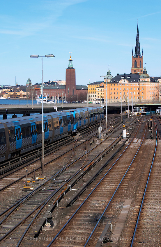 Blue train passing the bridge at Slussen with Riddarholmen and the Stadshuset in the background. The Stockholm subway. Kungsholmen Stockholm. Sweden, Europe.