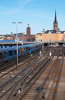 Blue train passing the bridge at Slussen with Riddarholmen and the Stadshuset in the background. The Stockholm subway. Kungsholmen Stockholm. Sweden, Europe.