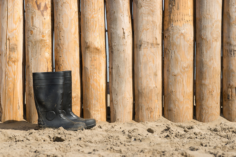 wheathered wood on beach and a pair of rubber boots