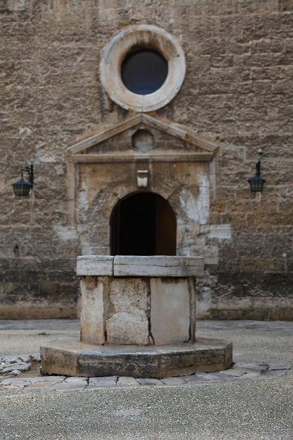 The typical ancient well, on the background of a decorated door with a round window over it, in the main court of the Normanno-Svevo (Swabian) castle, in the old part of the town, in Bari. The photo enhances the geometrical symmetries. Digitally Improved Photo.