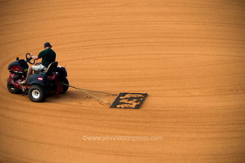 The grounds crew rakes the infield at Generals Park in Jackson, Tennessee.