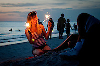 Teen plays with sparklers before the annual fireworks show at historic Naples Fishing Pier along Gulf of Mexico, Naples, Florida, USA, July 4, 2011. Photo by Debi Pittman Wilkey