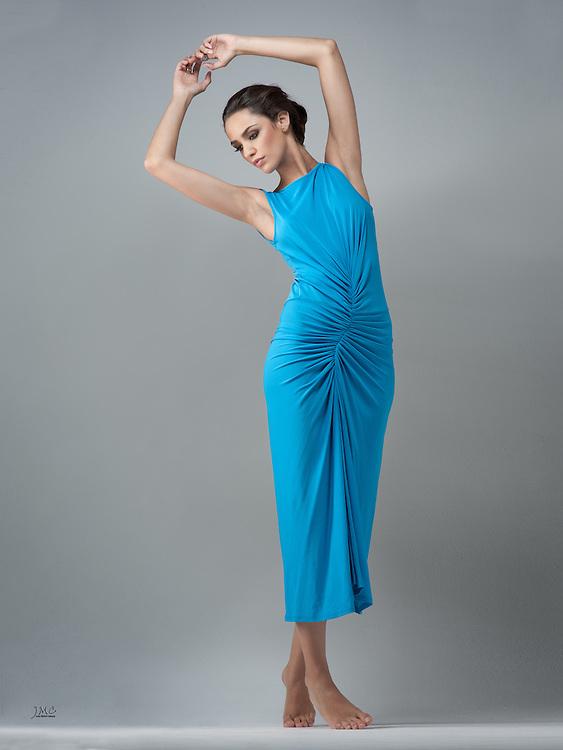 Beautiful brunette fashion model barefoot in light blue gown