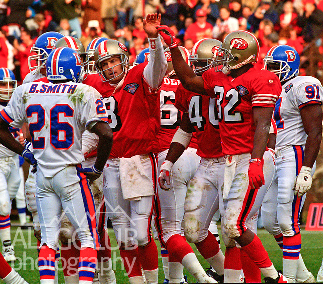 San Francisco 49ers vs. Denver Broncos at Candlestick Park Saturday, December 17, 1994.  49ers beat Broncos 42-19.  San Francisco 49ers quarterback Steve Young (8) and running back Ricky Watters (32) high five after play.