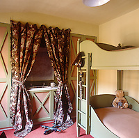 Curtains made of camouflage fabric screen the washbasin in this boy's bedroom
