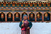 Woman holding prayer wheel at Kyichu Temple, Paro, Bhutan