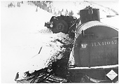 Engine #497 lying on side in the snow.  Tank UTLX 11047 end view to front of engine.<br /> D&amp;RGW  Cumbres area, CO