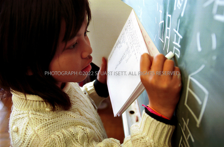 3/14/2000--Sagamihara City, Japan..9 year old Sirinthon Dwangchai (girl, center) from Laos at school at the Oshima Elementary School in Sagamihara practises her Kanji. The city was chosen as a relocation center for some 10,000 Southeast Asia refugees. Foreign children in Japan often face discrimination and bullying in Japanese schools where many Japanese still cling to their cherished ideal of Japan as a homogenous society...All photographs ©2003 Stuart Isett.All rights reserved.This image may not be reproduced without expressed written permission from Stuart Isett.