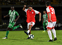 BOGOTA-COLOMBIA, 17-10-2019: Ronaldinho Gaucho ex jugador brasilero y Yilmar Velásquez de Atlético Nacional disputan el balón durante un partido de exhibición entre Independiente Santa Fe y Atlético Nacional en el estadio Nemesio Camacho El Campín en la ciudad de Bogotá. / Ronaldinho Gaucho Brazilian former player and Yilmar Velasquez of the Atletico Nacional team, fight for  the ball during an exhibition match againts Atletico Nacional at the Nemesio Camacho El Campin stadium in Bogota city. / Photo: VizzorImage / Luis Ramirez / Staff.