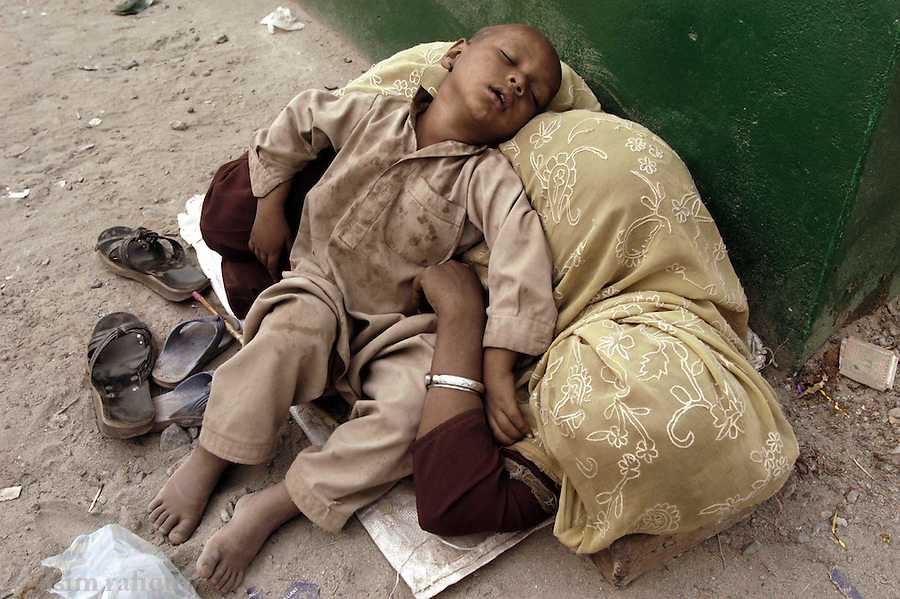 bari imam shrine, islamabad pakistan 2004: a mother and child pilgrims catch up on their sleep after a night of prayers and singing.  hundreds of thousands will come to the annual 'urs' of the bari imam from villages and towns all across the country.<br />