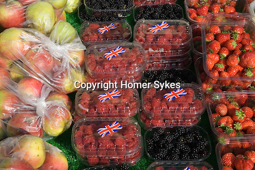 Bags of apples and British Raseberrys with Union Jack sticker. Wild Blackberrys and Strawberrys displayed on market stall.  Blackheath Farmers Market. South East London. UK 2008.