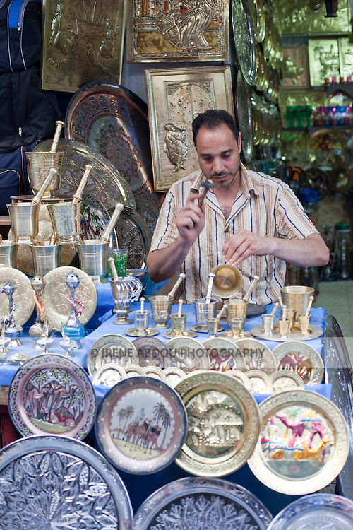 A man in the Medina (old city) in Tunis, Tunisia fashions souvenirs out of metal.