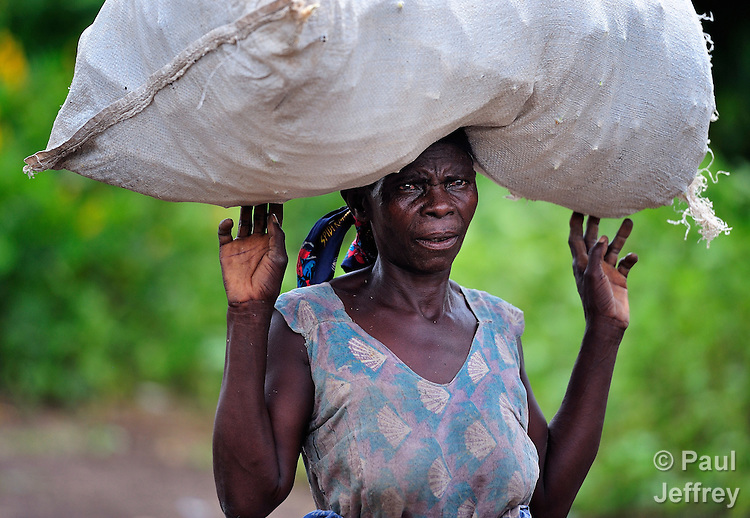 """A woman carries a bag on her head as she walks in Chidyamanga, a village in southern Malawi that has been hard hit by drought in recent years, leading to chronic food insecurity, especially during the """"hunger season,"""" when farmers are waiting for the harvest."""