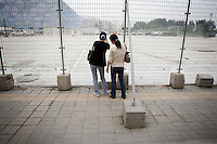 """CHINA. Beijing. People peer through a fence, trying to catch a glimpse of the new Olympic park. In recent years construction has boomed in Beijing as a result of the country's widespread economic growth and the awarding of the 2008 Summer Olympics to the city. For Beijing's residents however, it seems as their city is continually under construction with old neighborhoods regularly being razed and new apartments, office blocks and sports venues appearing in their place. A new Beijing has been promised to the people to act as a showcase to the world for the 'new' China. Beijing's residents have been waiting for this promised change for years and are still waiting, asking the question """"Where's the new Beijing?!"""". 2008."""