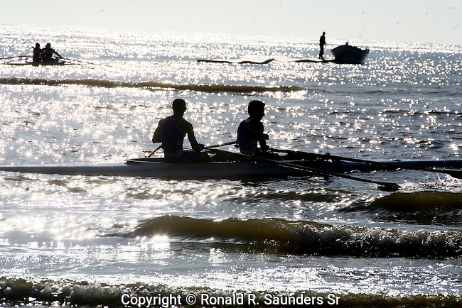 ROWERS SILHOUETTED AGAINST the SEA COMPETE in the LATIN AMERICAN WATER OLYMPICS