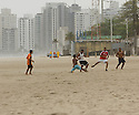 Locals playing soccer  on the beach in Guaruja, Brazil.