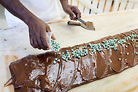 Daniel Ferguson, 50, shapes a log of Chocolate Mint fudge at Murdick's Fudge in Edgartown, Martha's Vineyard, Massachusetts, USA, on Tues., July 25, 2017.  Ferguson is from Jamaica and has an H2B seasonal foreign worker visa. He says 2017 is his sixth summer season working in the fudge shop. During off-months, he returns to Jamaica where he can be with family and escape the cold weather. Most of the shop's workers are seasonal foreign workers. Other companies on Martha's Vineyard and around the US had difficulty obtaining H2B visas, but Murdick's Fudge received all it requested.