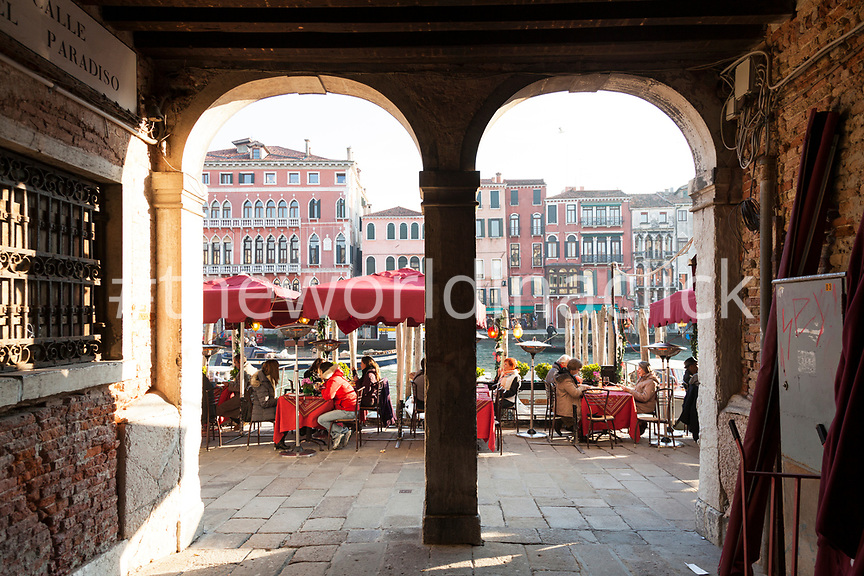 ITALY, Venice. Tourists eating lunch on Riva del Vin along the Grand Canal by the Rialto Bridge.