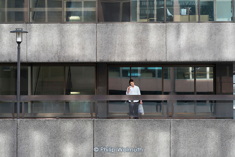 Man speaks on a mobile phone outside a City of London office block