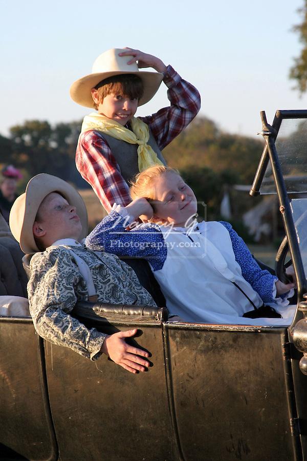Children enjoying a joy ride in an old car.