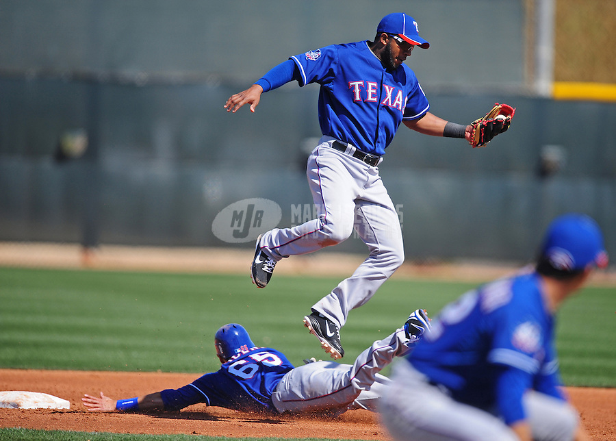 Mar. 2, 2012; Surprise, AZ, USA; Texas Rangers shortstop Elvis Andrus leaps as baserunner Greg Miclat slides safely into second with a stolen base during an intrasquad game on the practice fields at Surprise Stadium.  Mandatory Credit: Mark J. Rebilas-.