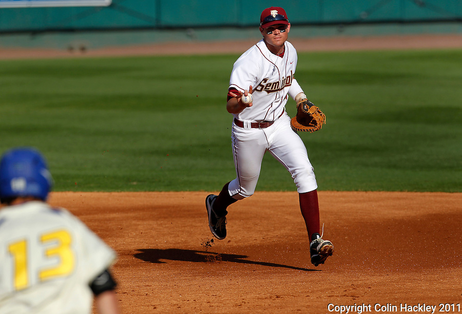 TALLAHASSEE, FL 2/26/11-FSU-HOFSTRA BASE11 CH-Florida State's Jayce Boyd, right, signals to Hofstra's Logan Davis that he has the ball as he trots to make the out at first Saturday at Dick Howser Stadium in Tallahassee. The Seminoles beat the Pride 16-3...COLIN HACKLEY PHOTO