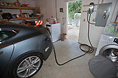 Tesla electric car recharging in garage in Green home that is off the grid. Solar power and a rainwater harvesting system supply all the energy and water for this home in Los Angeles, California, USA