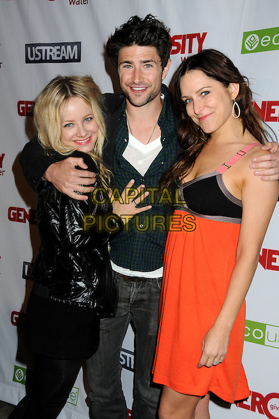 SAMANTHA MOLLEN, MATT DALLAS & JENNY MOLLEN.Generosity Water's 2nd Annual Night of Generosity held at the Mondrian Hotel's Skybar, West Hollywood, California , USA, 22nd March 2010..half length gold necklace jeans shiny beard facial hair black pink red dress strap white t-shirt jacket arm around hug hugging sisters sister family siblings .CAP/ADM/BP.©Byron Purvis/AdMedia/Capital Pictures.