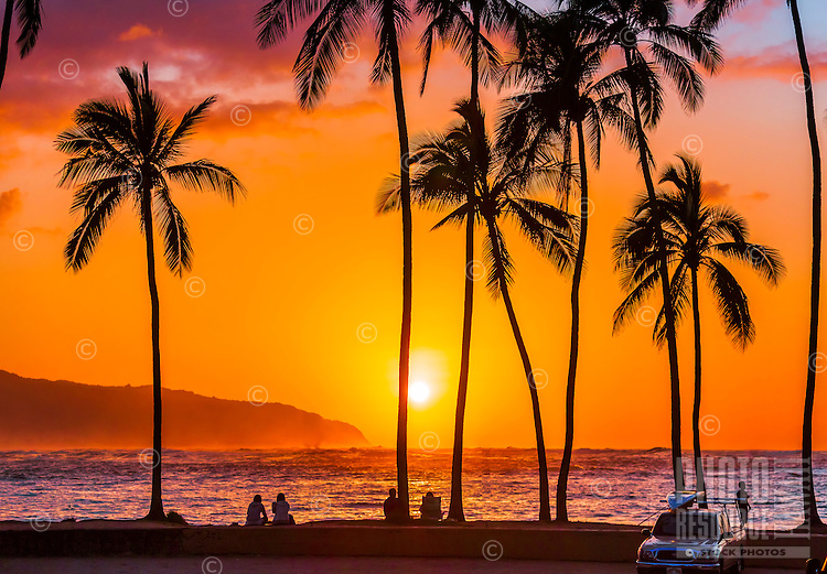 Locals and tourists watch the sun set from Haleiwa Beach Park, North Shore, O'ahu.