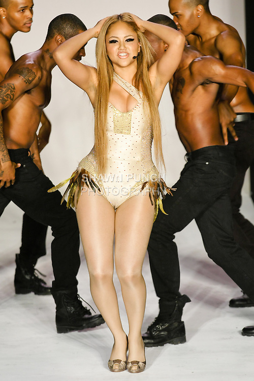 "R&B singer Kat DeLuna performs the world premiere of ""Dancing Tonight"", in an asymmetrical Swarovski crystalized rayon lycra bodysuit with gold sequined combo and feathers designed by Sachika, at the Sachika Fall 2011 ""The Awakening Of A Swan"" collection, at the Style 360 Fall 2011 fashion show, during New York Fashion Week."