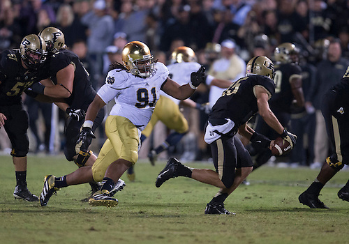 September 14, 2013:  Purdue quarterback Rob Henry (15) escapes the rush of Notre Dame defensive lineman Sheldon Day (91) during NCAA Football game action between the Notre Dame Fighting Irish and the Purdue Boilermakers at Ross-Ade Stadium in West Lafayette, Indiana.  Notre Dame defeated Purdue 31-24.