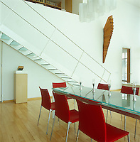 A long glass table and red chairs in the dining area of the open-plan double-height living space is approached by a glass staircase from the mezzanine