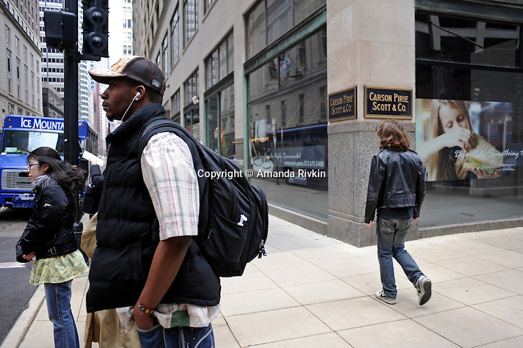 Pedestrians are seen on the street outside the Carson, Pirie, Scott and Company Building, a Chicago landmark, at 1 S. State St. in Chicago, Illinois on March 23, 2009.